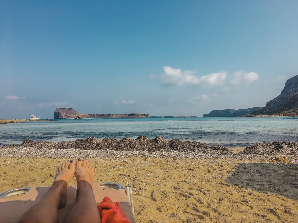 me laying out in the sand with views of balos