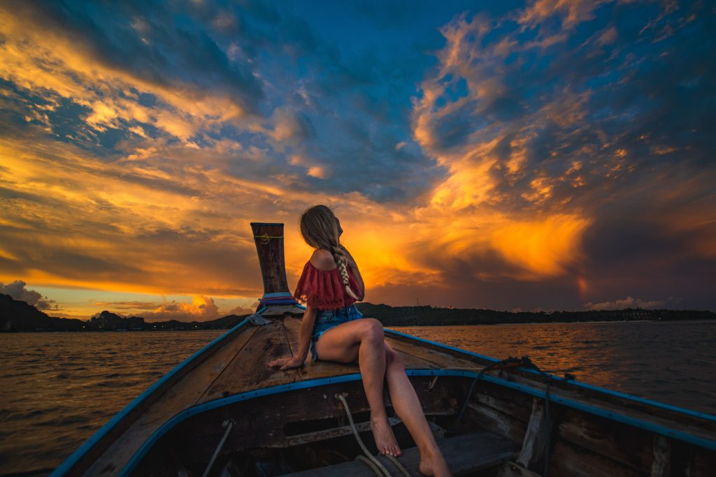 me on the long tail wooden boat by sunset