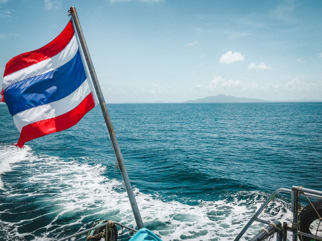 views over the sea off the back of the ferry with the thailand flag