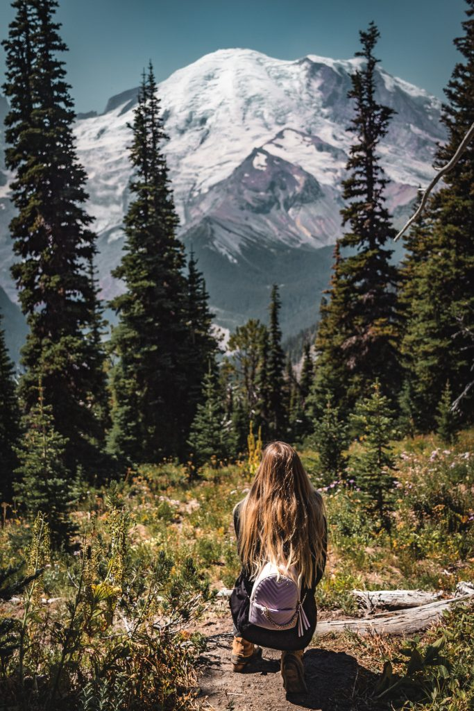 me squatting down for a photo in front of mount rainier