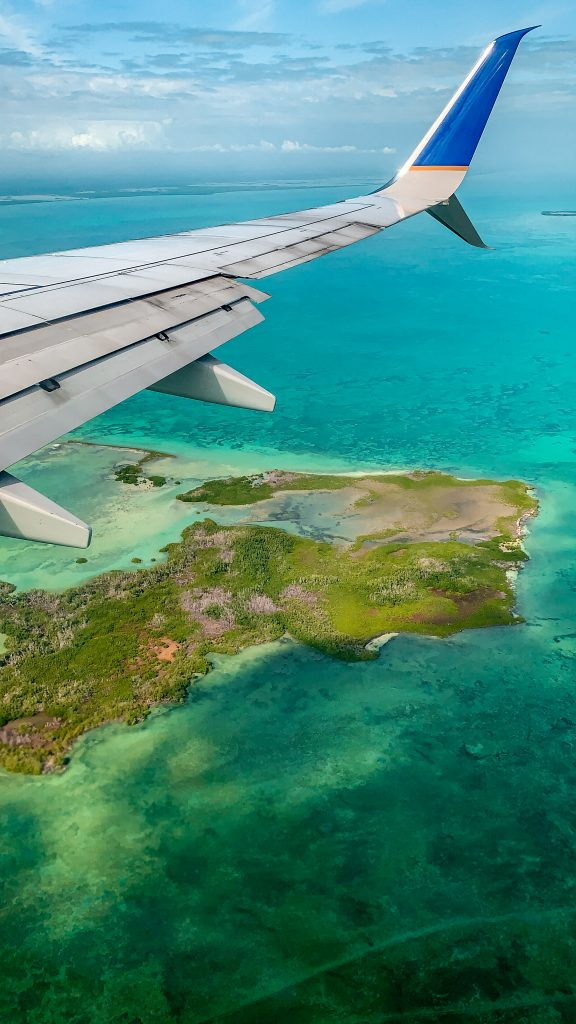 flying into belize with the water and islands under the plane wing