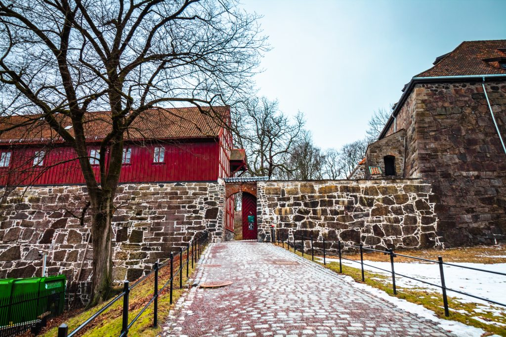 walking through the cobblestone walkway through the red door of the fortress brick wall
