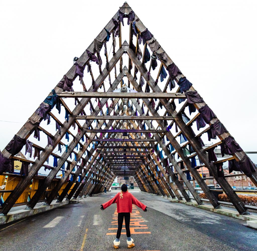 the big beamed triangle with shirts hanging off of it and me standing under it